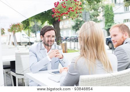 Happy businessman discussing with colleagues at sidewalk cafe