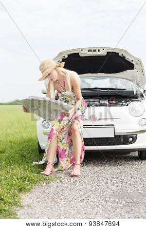 Woman reading map while sitting on broken down car at countryside