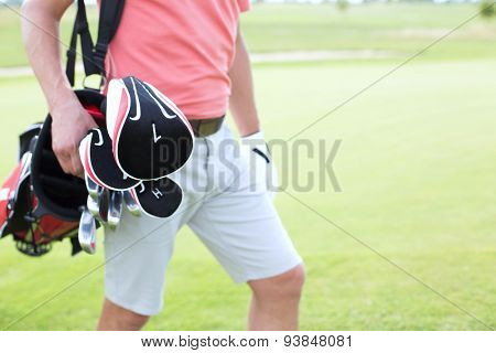 Midsection of man carrying golf club bag at course