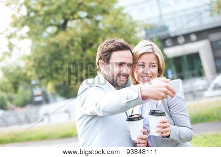 Happy business couple taking selfie while holding disposable cups in city