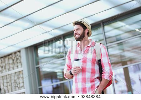 Happy man looking away while holding disposable cup in city