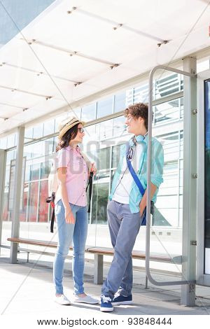 Couple communicating while waiting at bus stop