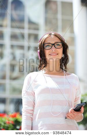 Thoughtful woman looking away while listening music outdoors