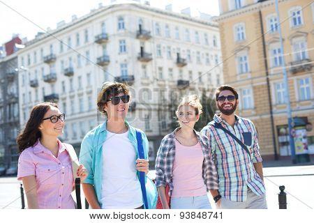 Happy male and female friends walking on city street