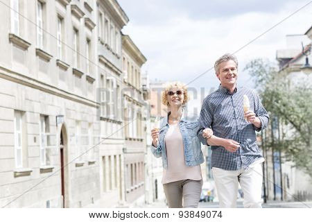 Happy middle-aged couple holding ice cream cones while walking in city