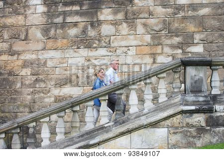 Side view of middle-aged couple climbing steps outside old building