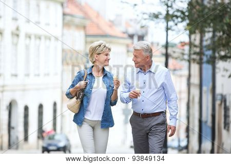 Happy middle-aged couple looking at each other while holding ice cream cones in city