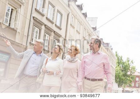 Middle-aged man showing something to friends while walking in city