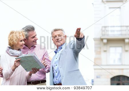 Man showing direction to couple with road map in city