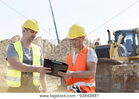 Engineers reading clipboard at construction site against clear sky