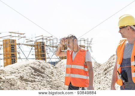 Construction worker looking at tired colleague wiping sweat at site