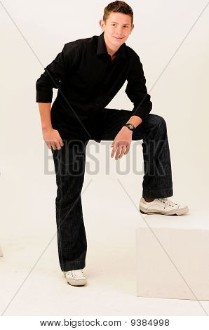 short haired teenager standing with one leg on step