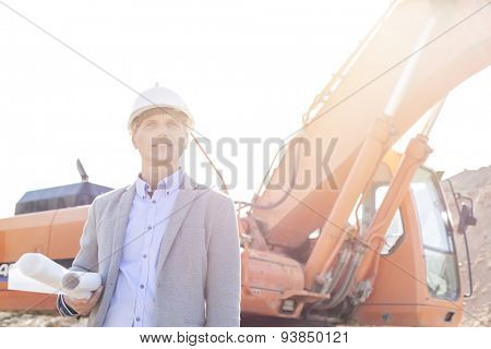 Thoughtful engineer looking away while holding blueprints by bulldozer at construction site