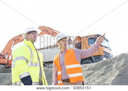 Engineer showing something to colleague while discussing at construction site against clear sky