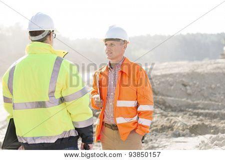 Supervisors discussing at construction site on sunny day