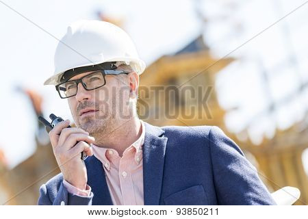 Male supervisor using walkie-talkie at construction site