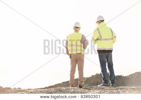 Rear view of architects standing at construction site against clear sky