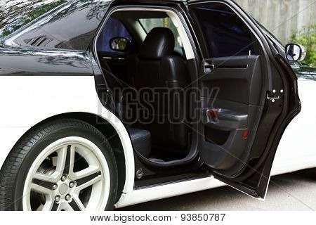 Modern car with open door outdoors