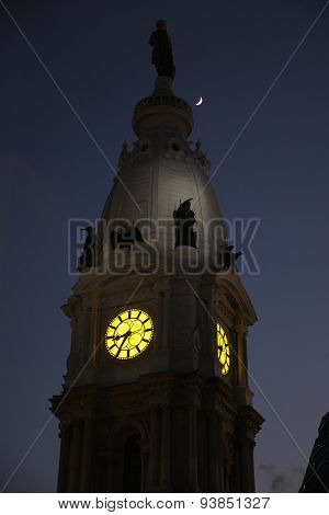 The Philadelphia City Hall clock tower at night with a crescent moon in the sky