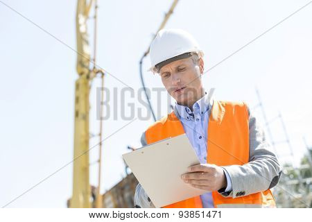 Low angle view of supervisor writing on clipboard at construction site