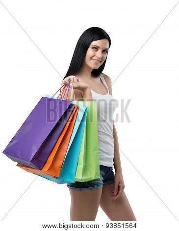 A Happy Brunette Woman With The Colourful Shopping Bags From The Fancy Shops. Isolated.