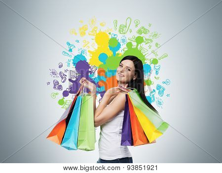 Beautiful Smiling Young Woman With The Colourful Shopping Bags From The Fancy Shops. Studio Backgrou