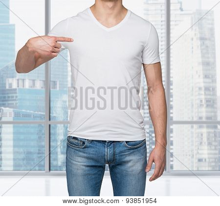 Close-up Of A Man Pointing His Finger On A Blank T-shirt. New York Panoramic View In A Modern Office