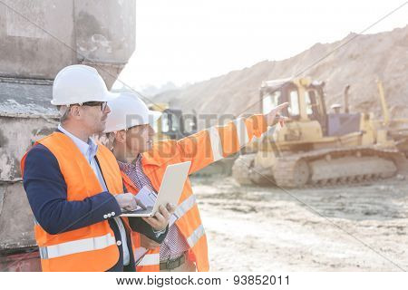 Supervisor showing something to coworker holding laptop at construction site