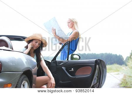 Woman using cell phone in convertible while friend reading map on road
