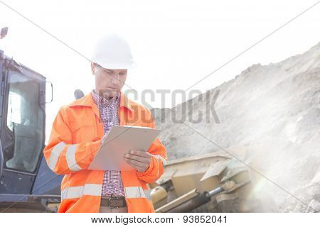 Engineer reading clipboard at construction site