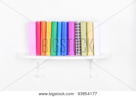 Colorful books on shelf on white wall background
