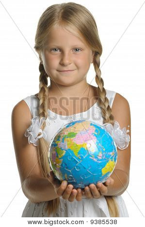 The Girl Holds The Globe Collected From Puzzle In Hands. Selective Focus