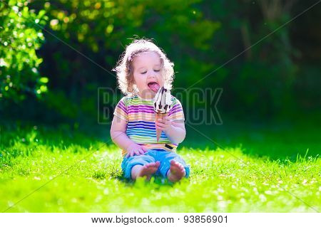 Little Girl Eating Ice Cream In The Garden