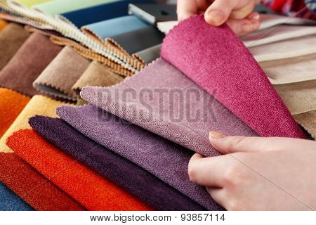 Woman chooses scraps of colored tissue on table close up
