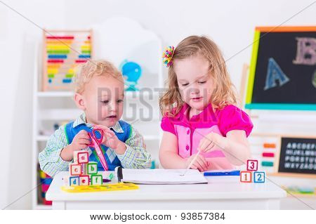 Kids at preschool. Two children drawing and painting at kindergarten