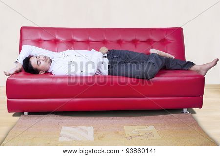 Man Napping On The Red Sofa
