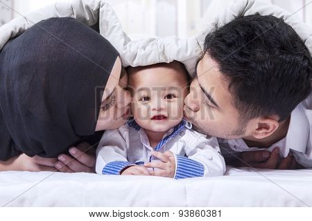 Muslim Parents Kiss Their Baby Under Blanket