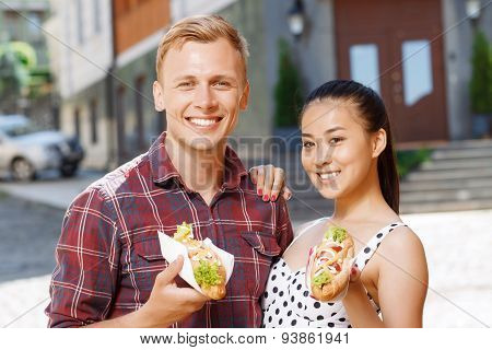 Young man and woman with hotdogs on street
