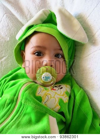 Portrait of a baby boy in a rabbit costume with a baby's dummy in his mouth