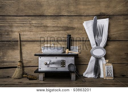 Old miniature of an oven with cutlery on an ancient rustic background for a menu card.