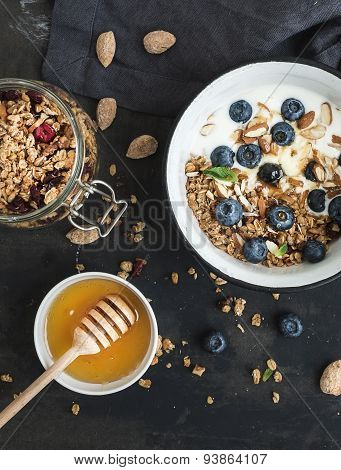 Healthy breakfast. Oat granola with fresh blueberries, almond, yogurt and mint in a rustic metal bow