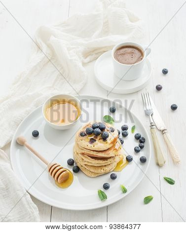 Breakfast set. Blueberry pancakes with fresh berries, honey, mint leaves and cup of coffee over whit