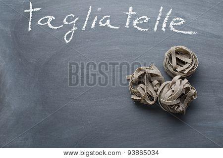 the black tagliatelle pasta on chalkboard