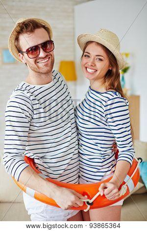 Happy couple looking at camera inside buoy