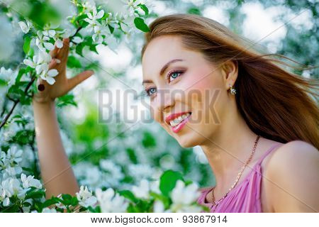 beautiful young woman with apple trees in the park in summertime