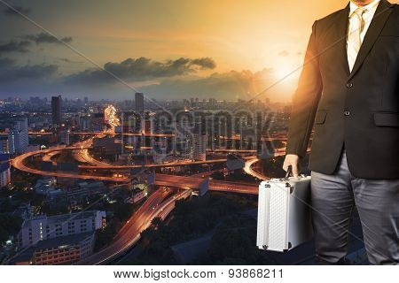 Business Man And Metal Briefcase Luggage In Hand Standing Against Express Way Of Capital Town And Su