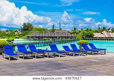 Wooden lounge chairs on on a wooden pier at Maldives