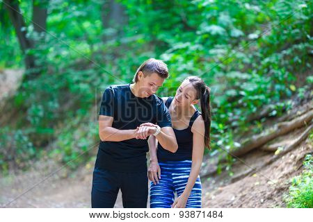 Young active couple looking at smart watch heart rate monitor having break while running at forest