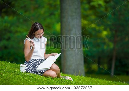 Young girl writing in her notebook outside at park