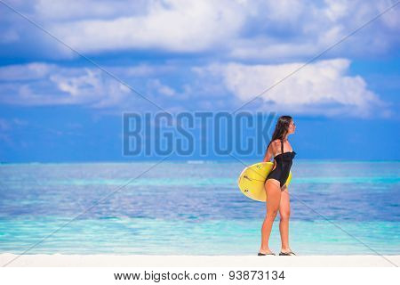 Happy slender surf woman at white beach with yellow surfboard